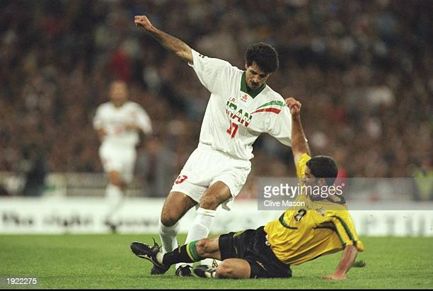 Ali Daei of Iran is tackled by Craig Foster of Australia during the World Cup qualifier in Melbourne Australia The game ended 22 and Iran qualified...