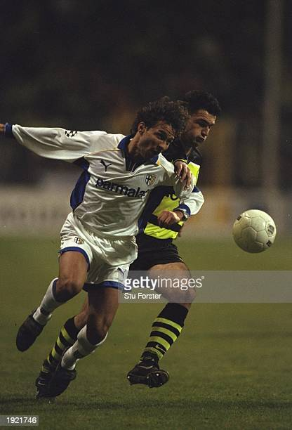 Antonio Benarrivo of Parma and Stephane Chapuisat of Borussia Dortmund compete for the ball during the UEFA Champions League match at the...