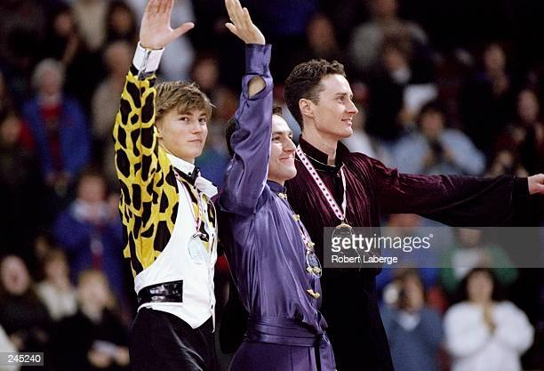 Elvis Stojko of Canada Ilia Kulik of Russia and Michael Tyllesen of Denmark celebrate on the podium after the men''s singles competition at the Sun...