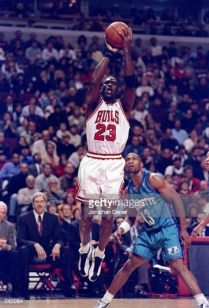 Guard Michael Jordan of the Chicago Bulls in action against guard Bobby Phills of the Charlotte Hornets during a game at the United Center in...
