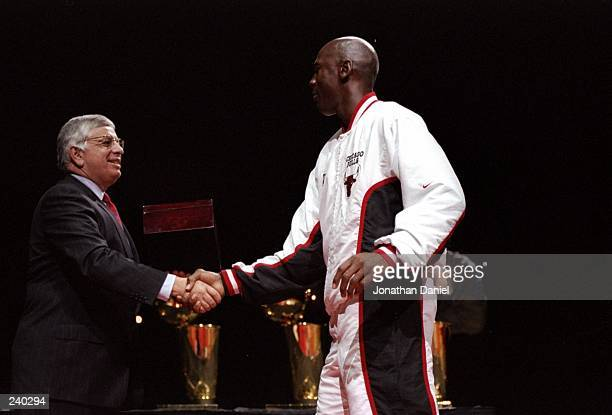 Guard Michael Jordan of the Chicago Bulls shakes hands with David Stern during the presentation of championship rings prior to a game against the...