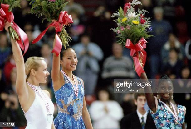 Michelle Kwan of the USA Maria Butyrskaya of Russia and Surya Bonaly of France celebrate on the podium after the women''s singles competition at the...