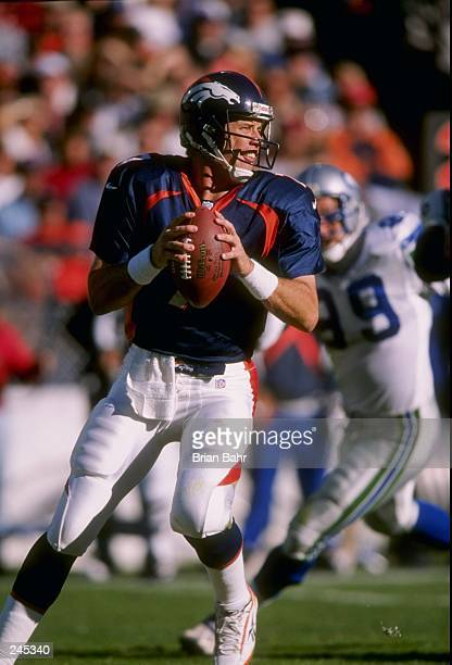 Quarterback John Elway of the Denver Broncos sets to throw a pass during the Broncos 3027 win over the Seattle Seahawks at Mile High Stadium in...