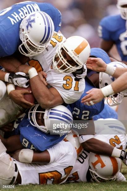 Running back Jamal Lewis of the Tennessee Volunteers is tackled by defensive tackle Marvin Major and Ryan Murphy of the Kentucky Wildcats during a...