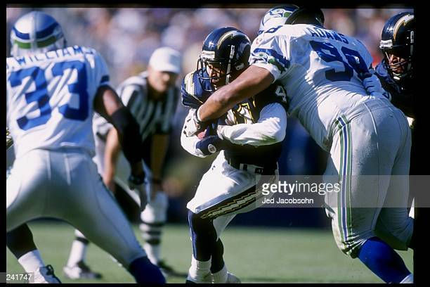 Running back Terrell Fletcher of the San Diego Chargers tries to run past defensive tackle Sam Adams of the Seattle Seahawks during a game at...