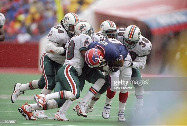 Wide receiver Andre Reed of the Buffalo Bills is gang tackled by Calvin Jackson #23 George Teague Derrick Rodgers and Zach Thomas of the Miami...