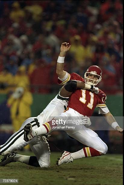 Quarterback Elvis Grbac of the Kansas City Chiefs getting tackled by Anthony Pleasant during the game against the New York Jets at the Arrowhead...