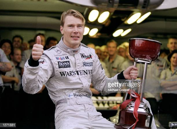 Race winner Mika Hakkinen of Finland racing for Mercedes McLaren poses for pictures after the Japanese Grand Prix at the Suzuka circuit in Suzuka...