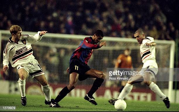 Rivaldo of Barcelona twists between Paul Scholes and Roy Keane of Manchester United during the UEFA Champions League match at the Nou Camp in...