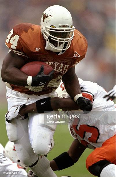 Tailback Ricky Williams of the Texas Longhorns runs with the ball during a game against the Oklahoma State Cowboys at the Texas Memorial Stadium in...