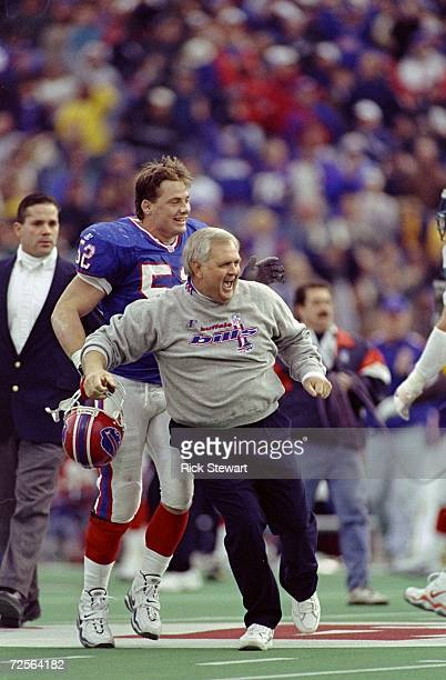 Wade Phillips head coach of the Buffalo Bills run as he celebrates during a game against the Miami Dolphins at Rich Stadium in Orchard Park New York...