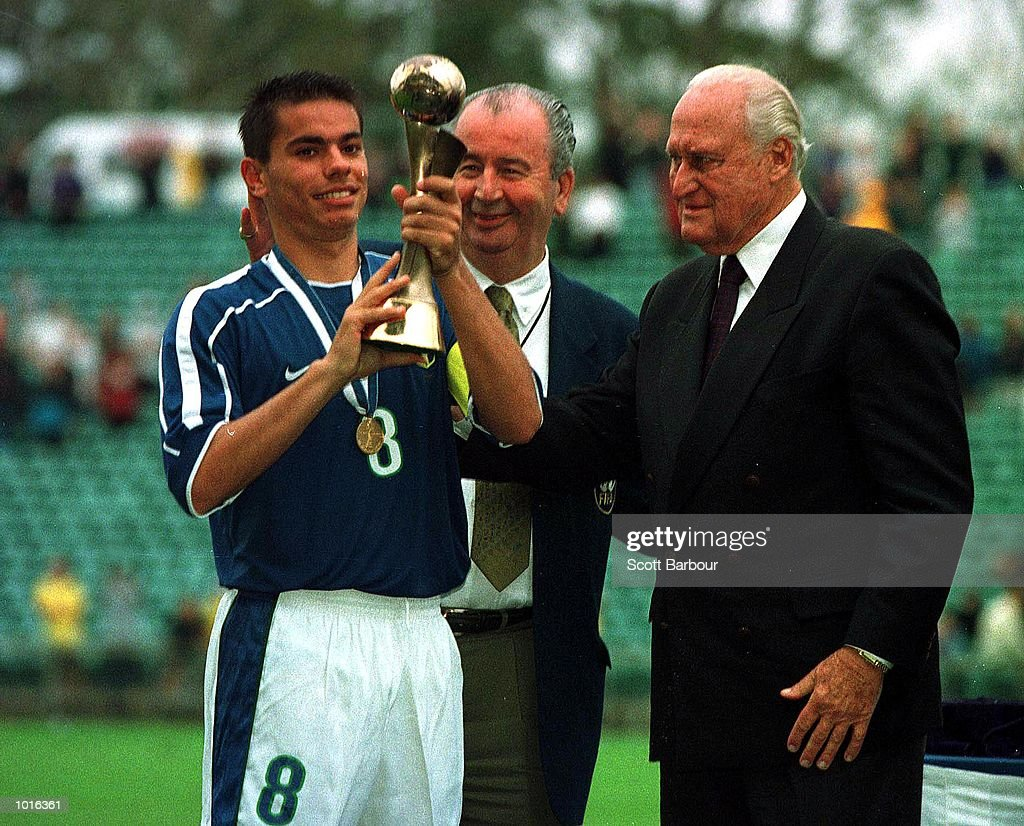 Brazil captain Walker is presented with the World Cup by Charlie Dempsey and Joao Havelange as Brazil win the FIFA Under 17 World Cup soccer final at the North Harbour Stadium, Auckland, New Zealand. Mandatory Credit: Scott Barbour/ALLSPORT