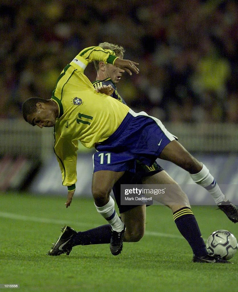 Brazil's #11 Denilson crashes to the ground after a heading contest with Australia's #6 Josip Skoko during the first half of the Socceroos v Brazil game, played at the MCG, Melbourne, Victoria, Australia. The Socceroos led 1-0 at half time.X Mandatory Credit: Mark Dadswell/ALLSPORT