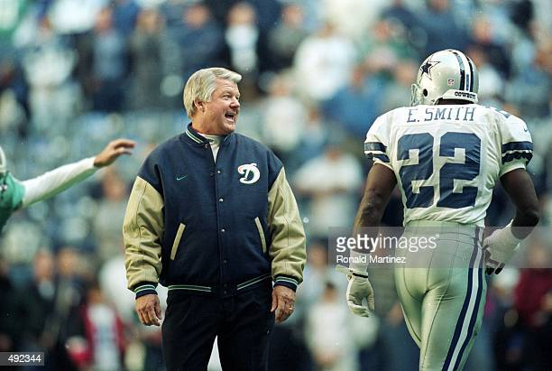 Coach Jimmy Johnson of the Miami Dolphins talks to Emmitt Smith of the Dallas Cowboys as he walks onto the field during the game at the Texas Stadium...