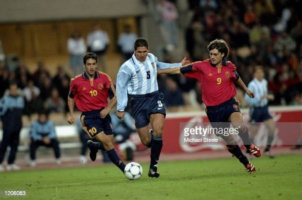 Diego Simeone of Argentina is chased by Raul and Julen Guerrero of Spain during the International Friendly played at the Estadio Olympico in Seville...