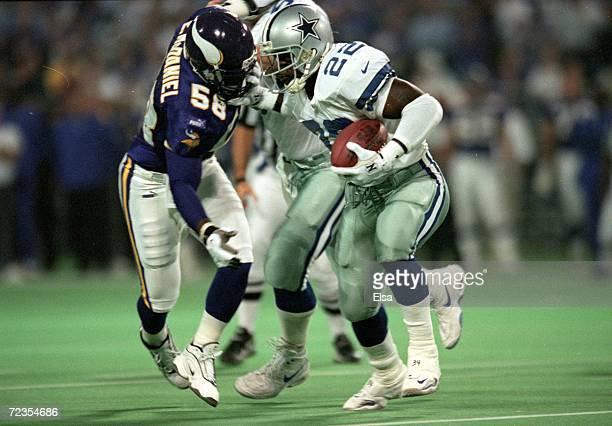 Emmitt Smith of the Dallas Cowboys moves with the ball as Ed McDaniel of the Minnesota Vikings tries to tackle him during the game at the Herbert H....