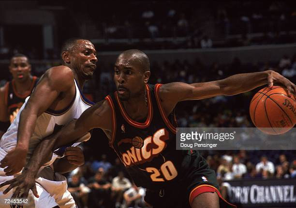 Gary Payton of the Seattle SuperSonics takes the ball to the basket as he is blocked by Chris Whitney of the Washington Wizards at the MCI Center in...