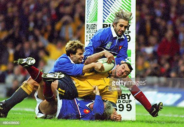 Joe Roff of Australia is tackled short of the try line during the Final of the 1999 Rugby World Cup against France played at the Millennium Stadium...