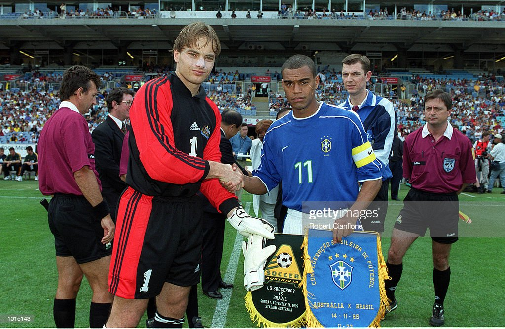 Mark Bosnich of Australia (L) in his first game as captain shakes hands with Denilson of Brazil before the friendly soccer game played at Stadium Australia, Homebush, Sydney, Australia. Brazil won 2-0. Mandatory Credit: Robert Cianflone/ALLSPORT