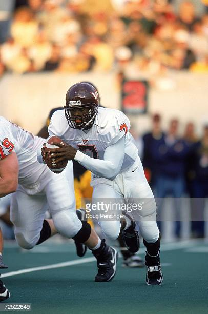 Michael Vick of the Virginia Tech Hokies scrambles with the ball during a game against the West Virginia Mountaineers at Mountaineer Field in...