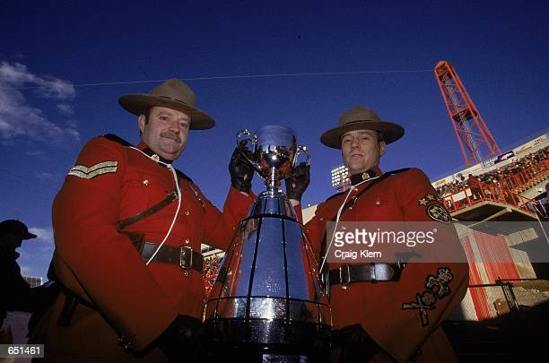 A view of two Mounties posing with the Grey Cup before the Grey Cup 2000 game between the British Columbia Lions and the Montreal Alouettes at the...