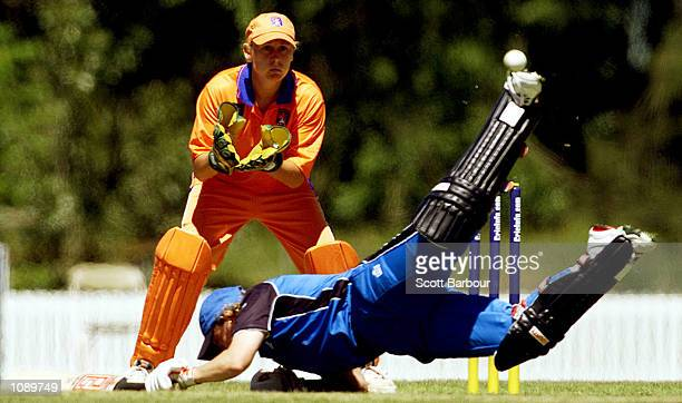 Barbara Daniels of England dives back to make her ground as Netherlands wicketkeeper Rowan Milburn waits for the ball during the England v...