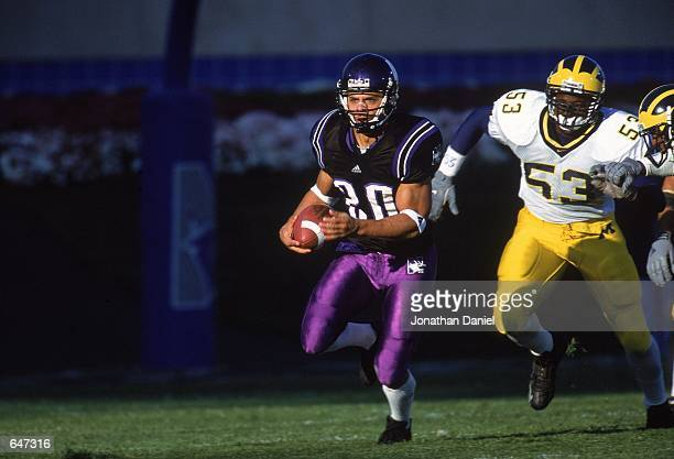 Damien Anderson of the Northwestern Wildcats runs away with the ball during the game against the Michigan Wolverines at the Ryan Field in Evanston...