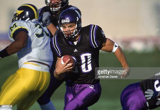 Damien Anderson of the Northwestern Wildcats runs with the ball through the melee during the game against the Michigan Wolverines at the Ryan Field...