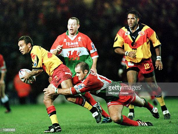 Dean Busby of Wales tackles Adrian Lam of PNG during the Wales v Papua New Guinea QuarterFinal match at the Auto Quest Stadium Widnes Mandatory...