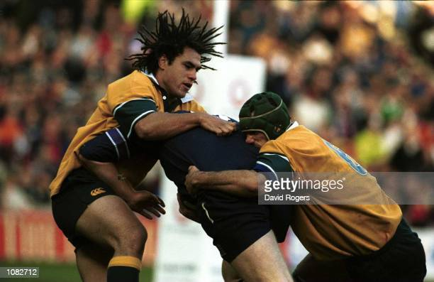 George Smith and Matt Cockbain of Australia tackle a Scottish player during the Famous Grouse rugby union international between Scotland and...