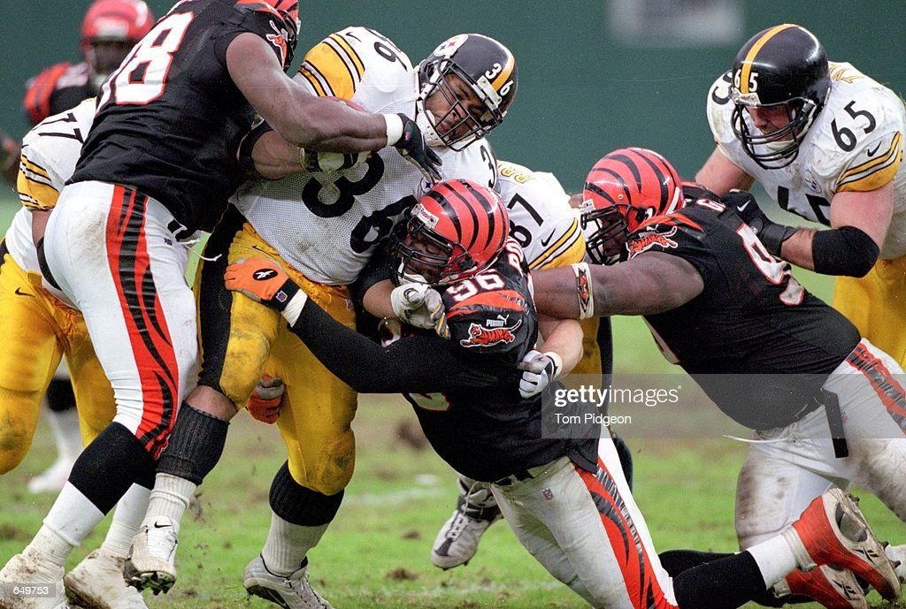 Jerome Bettis #36 of the Pittsburgh Steelers carries the ball as he is tackled by Vaughn Booker #96 of the Cincinnati Bengals at Paul Brown Stadium in Cincinnati, Ohio. The Steelers defeated the Bengals 48-28.Mandatory Credit: Tom Pidgeon /Allsport
