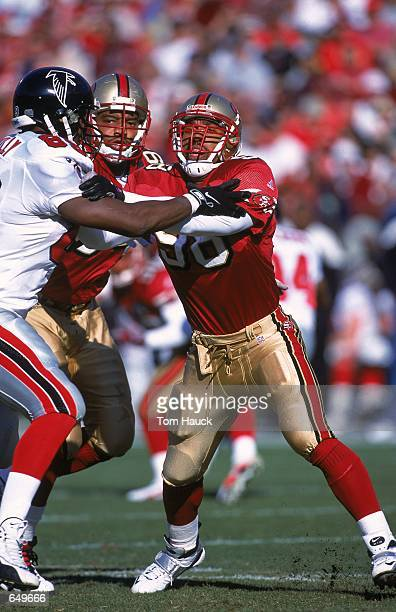 Julian Peterson of the San Francisco 49ers tries to hold back Reggie Kelly of the Atlanta Falcons during the game at 3Comm Park in San Francisco,...