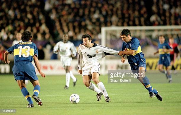 Luis Figo of Real Madrid is held back by Jose Basualbo of Boca Juniors during the 21st Toyota Cup European/South American Cup match between Boca...