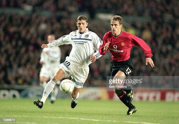 Maksim Shatskikh of Dynamo Kiev chases after the loose ball with Phil Neville of Manchester United during the UEFA Champions League match played at...