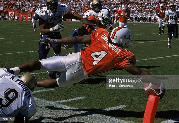 Najeh Davenport of the Miami Hurricanes makes a touch down as Amir Purifoy of the Pittsburgh Panthers tries to stop him during the game at the Orange...