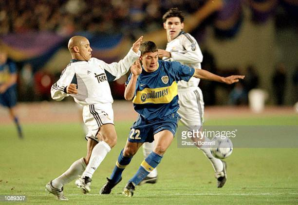 Roberto Carlos of Real Madrid challenges Sebastian Battaglia of Boca Juniors during the 21st Toyota Cup European/South American Cup match between...