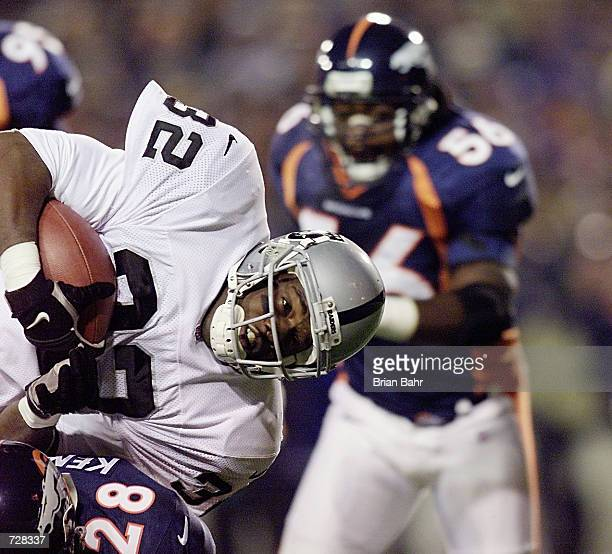 Running back Zack Crockett of the Oakland Raiders goes horizontal as safety Kenoy Kennedy of the Denver Broncos hits him and keeps him out of the...
