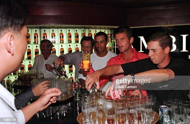 Tiger Woods of USA, Jesper Parnevik of Sweden and Sergio Garcia of Spain serve drinks behind the bar during the Johnnie Walker Golfers Round at the...