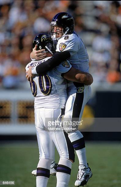 Trent Dilfer of the Baltimore Ravens celebrates with teammate Jeff Mitchell during the game against the Cincinnati Bengals at Brown Stadium in...