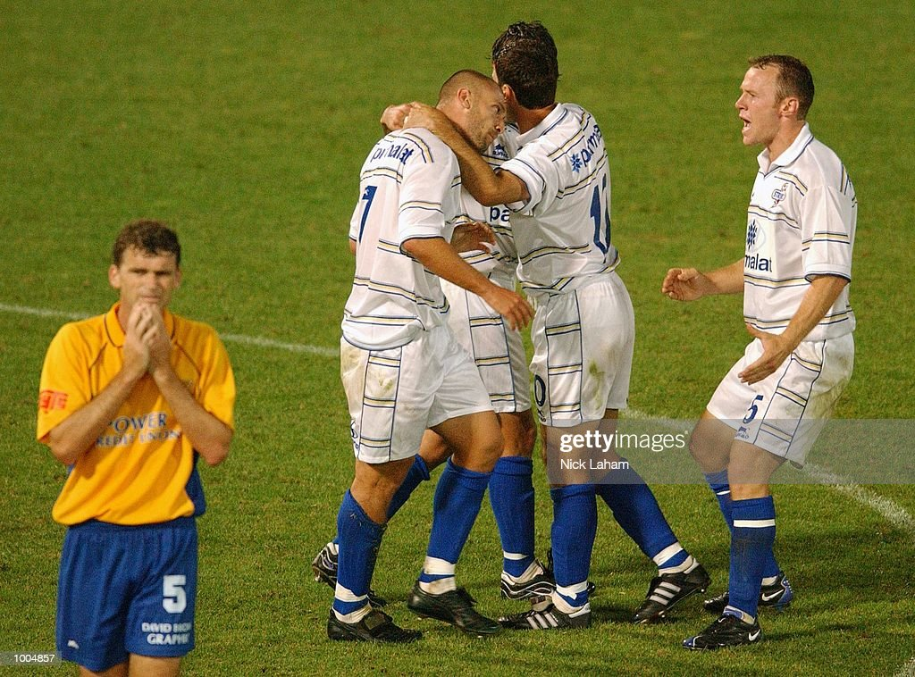 A dejected Alex Tobin #5 of the Power (l) walks from the Strikers celebrations after Fernando Rech's goal during the NSL match between the Parramatta Power and the Brisbane Strikers held at Parramatta Stadium, Sytdney, Australia. Strikers 2defeated the Power 1. DIGITAL IMAGE Mandatory Credit: Nick Laham/ALLSPORT