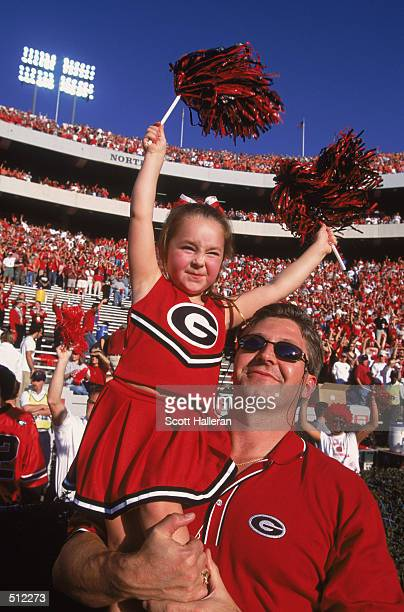 A young girl fan of the Georgia Bulldogs waves pom poms while being held by her dad at the SEC game between Georgia and the Auburn Tigers at Sanford...