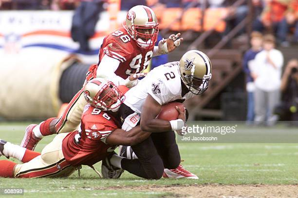 Aaron Brooks of the New Orleans Saints can''t shake the hold of Julian Peterson of the San Francisco 49ers during the game at 3 Com Stadium in San...