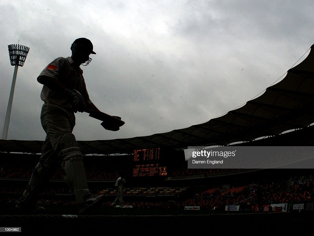 Adam Gilchrist of Australia leaves the field at lunch on 98 runs under rainy skies during day three of the first Cricket test between Australia and New Zealand played at the Gabba in Brisbane, Australia. DIGITAL IMAGE. Mandatory Credit: Darren England/ALLSPORT