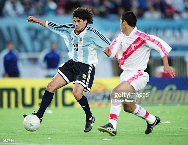Ariel Ortega of Argentina holds off the challenge from Jorge Huaman during the FIFA 2002 World Cup Qualifier between Argentina and Peru played at the...