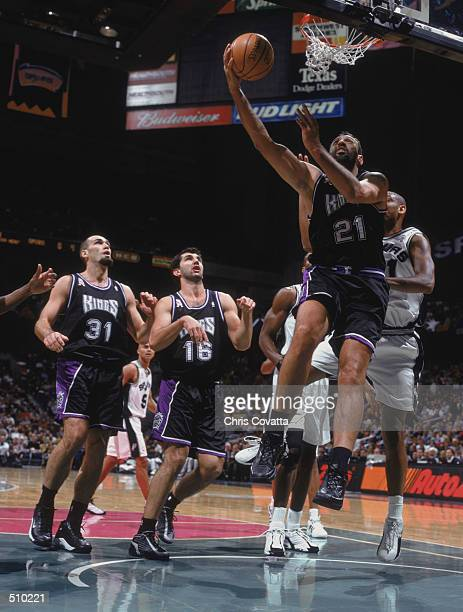 Center Vlade Divac of the Sacramento Kings shoots the ball as his two teammates guard Predrag Stojakovic and forward Scot Pollard stand under the...
