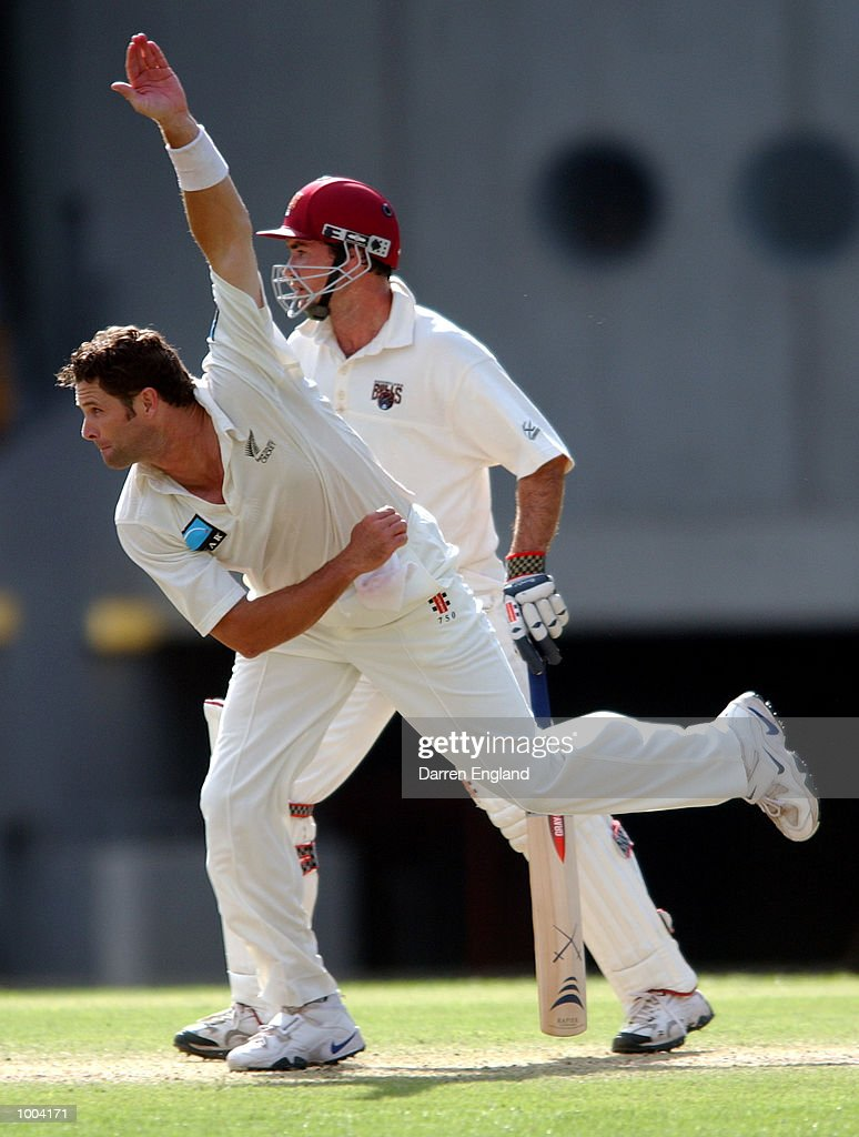 Chris Cairns of New Zealand in action bowling while Jimmy Maher of Queensland looks on during the New Zealand versus Queensland cricket match played at the Gabba in Brisbane, Australia. The match is part of the New Zealand team's tour of Australia. DIGITAL IMAGE. Mandatory Credit: Darren England/ALLSPORT