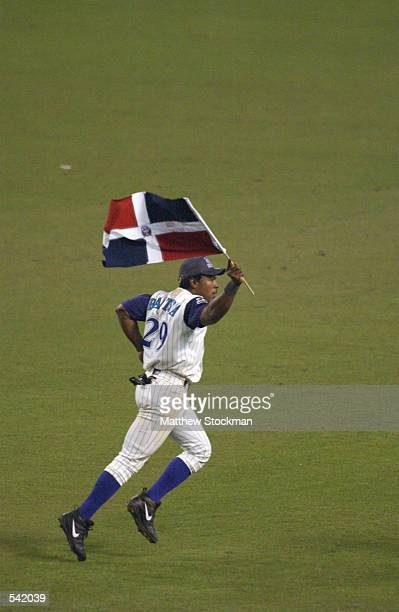 Danny Bautista of the Arizona Diamondbacks jogs through the outfield with the flag of his native Dominican Republic as he celebrates their victory...