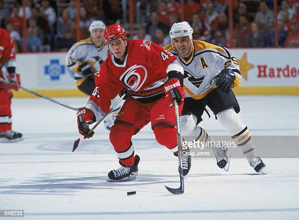 Defenseman David Tanabe of the Carolina Hurricanes races for the puck ahead of left wing Kevin Stevens of the Pittsburgh Penguins during the NHL game...