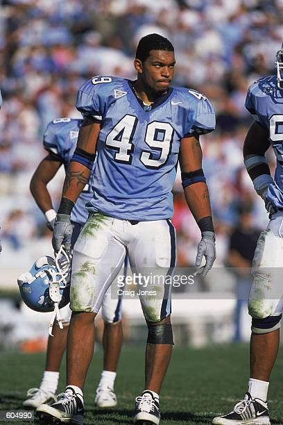 Defensive End Julius Peppers of the North Carolina Tar Heels holding hishelmet while standing on the field during the game against the Wake Forest...