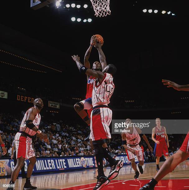 Forward Lamar Odom of the Los Angeles Clippers shoots over guard Walt Williams of the Houston Rockets during the NBA game at the Compaq Center in...